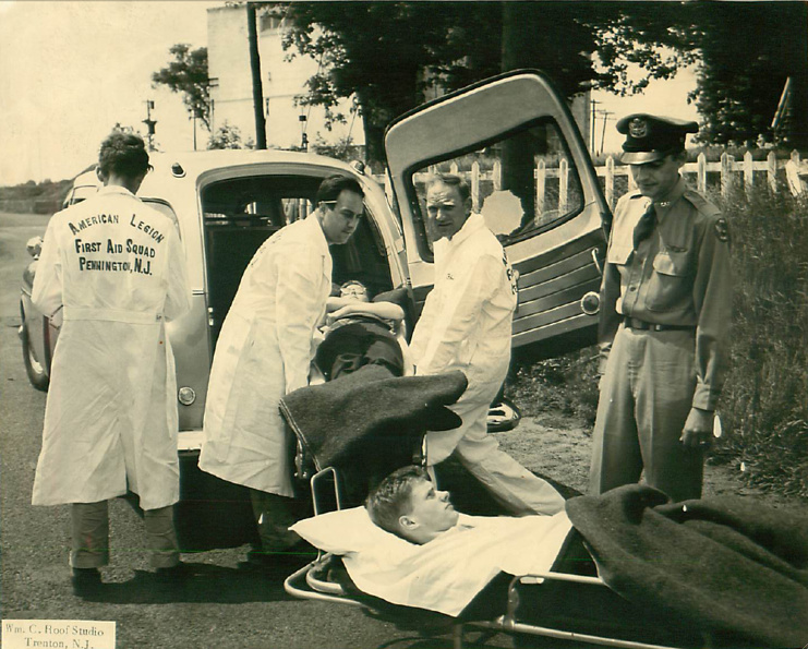 crew loading patients into Packard ambulance